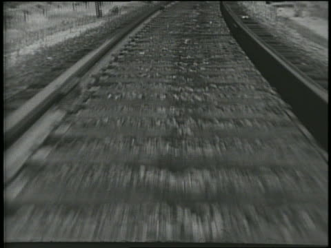 B/W low close up train point of view of train tracks / comes to a stop