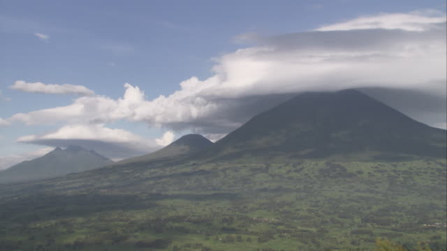 low clouds cast shadows over three volcanoes in the virunga mountains. available in hd. - nationalpark stock-videos und b-roll-filmmaterial