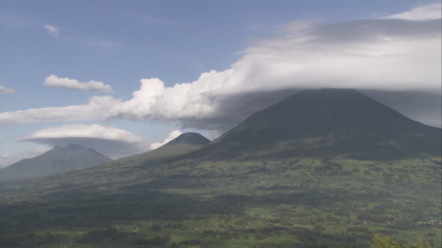 Low clouds cast shadows over three volcanoes in the Virunga Mountains. Available in HD.