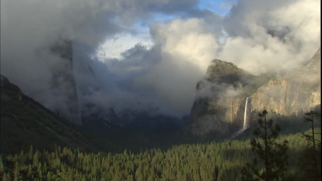 Low clouds cover Bridalveil Falls and Cathedral Rocks in Yosemite National Park, California.
