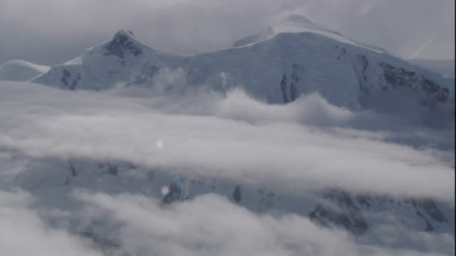 vídeos de stock, filmes e b-roll de low clouds encircle snow-blanketed mountains in antarctica. - pólo sul