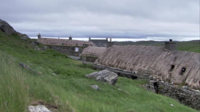 vídeos y material grabado en eventos de stock de low clouds loom above the black houses of gearrannan scotland. available in hd. - techo de paja