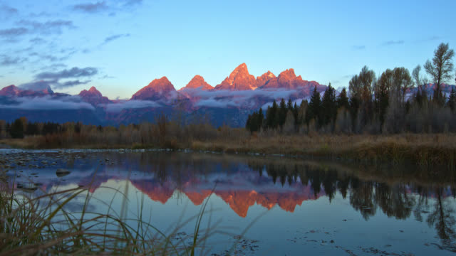 time lapse long wide shot low clouds pass in front of grand teton with reflection in lake in foreground at sunrise, wyoming - grand teton stock-videos und b-roll-filmmaterial