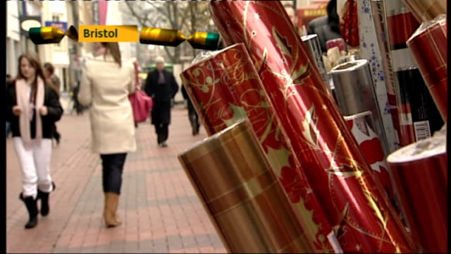 low consumer cofidence may hit christmas spending bristol shoppers along shopping street with display of christmas wrapping paper in foreground - christmas wrapping paper stock videos & royalty-free footage