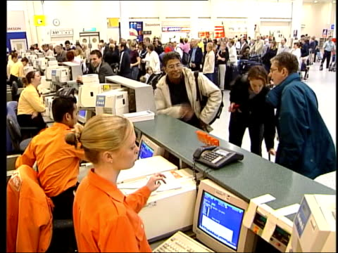 vídeos de stock e filmes b-roll de low cost airlines increase in popularity england london gatwick airport passengers queuing at easyjet check in desks in airport i/c easyjet worker... - veículo aéreo