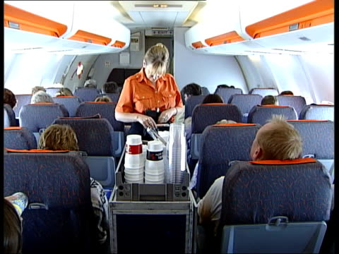 Low cost airlines increase in popularity i/c MS Passenger sitting in plane MS Stewardess serving passengers drinks from trolley MS Businessmen...