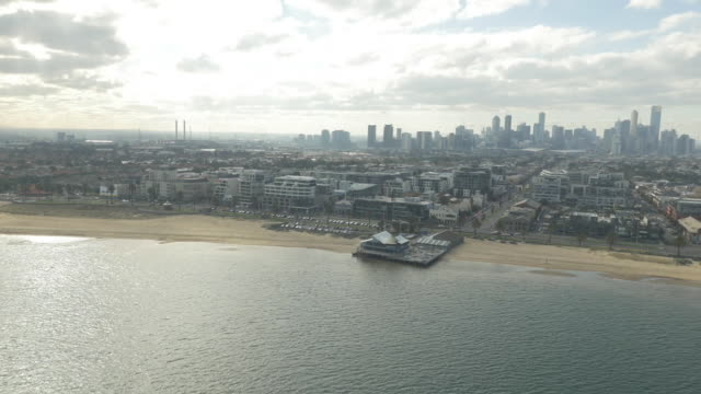 low drone aerial looking across suburban port melbourne to melbourne cbd skyline port melbourne yacht club in foreground - bay of water stock videos & royalty-free footage