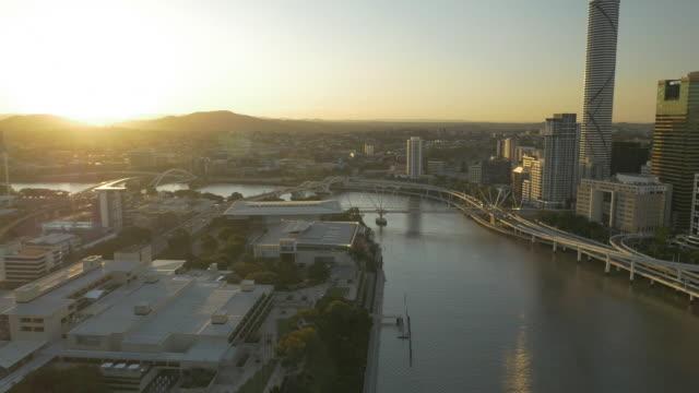 Low Drone Aerial Sunset North to east pan across Brisbane City skyline over arts precinct to city including Kurilpa Bridge Infinity Building Victoria...