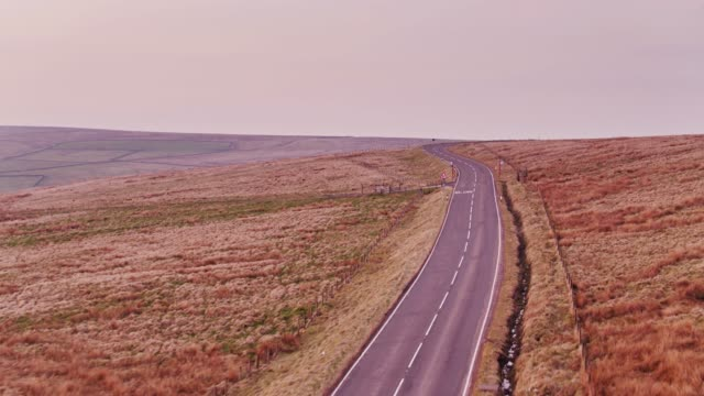 low drone flight over winding country road between oxenhope and hebden bridge, england - pennines stock videos and b-roll footage