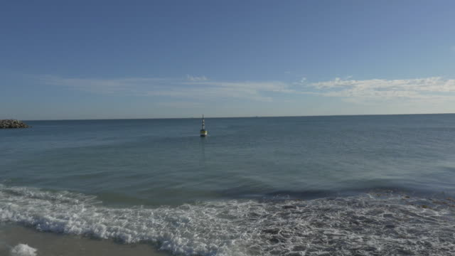 low Drone looking from water level west out to Indian Ocean gentle waves lapping seagulls flying Track out to water marker and 180 degree turn to see...