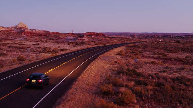 low drone shot of road through grand staircase escalante national monument at twilight - grand staircase escalante national monument stock-videos und b-roll-filmmaterial