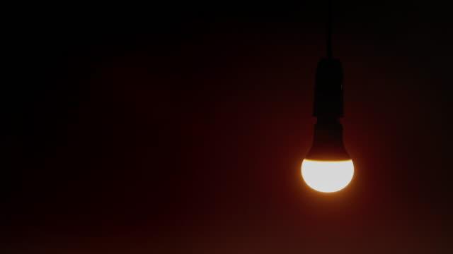low energy lightbulb. black background. - pendant light stock videos & royalty-free footage