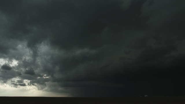 Low fast-moving thunderstorm rolls across prairie as headlights speed by at right, time lapse
