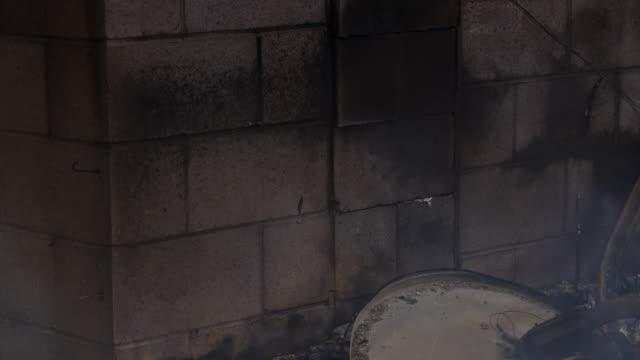 vidéos et rushes de low flames consume charred wood at the edge of a cinder block pillar amid the debris of a house fire - parpaing