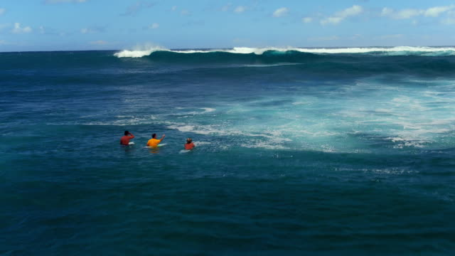 low fly over aerial shot of three surfers discussing the swell - kahuku stock videos & royalty-free footage
