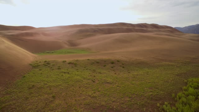 low fly over creek and up sand dunes - colorado stock videos and b-roll footage