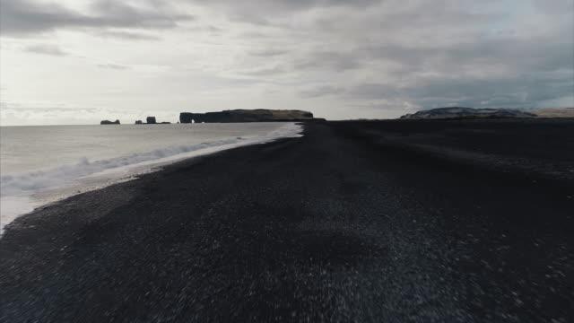 low flying drone shot across a black sand beach, reynisfjara, vik, iceland - island stock-videos und b-roll-filmmaterial