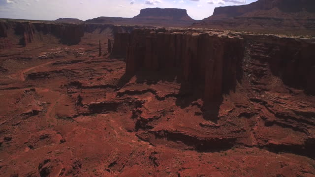 low flying over rocks tilt camera up to reveal the cannyonlands national park utah - キャニオンランズ国立公園点の映像素材/bロール