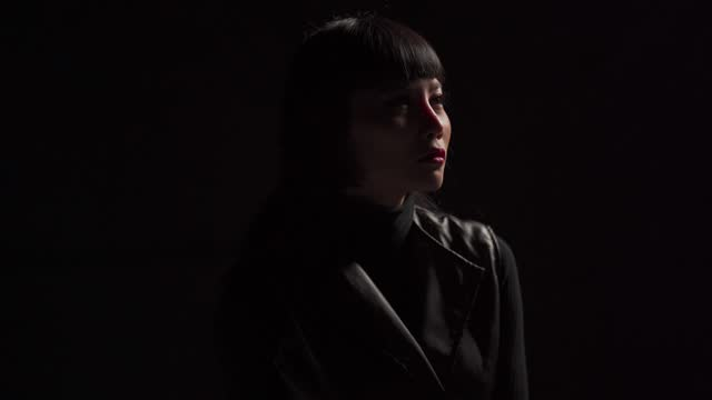 low key asian chinese female fashion model in studio portrait cool attitude black background - black background stock videos & royalty-free footage
