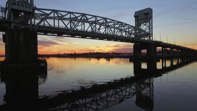 drone. low level aerial view from boat ramp of the cape fear memorial bridge as cars drive over during majestic sunset - wilmington north carolina stock-videos und b-roll-filmmaterial