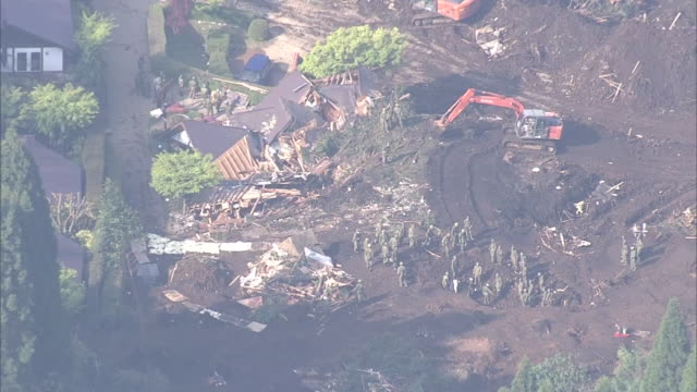 Low level aerial view of a group of rescuers and crane cars clearing debris and rescuing victims from buried houses in landslide affected area in...