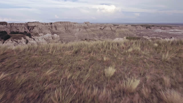 DRONE. Low level aerial view of grassy field opening up to a majestic view of prehistoric Badlands canyons