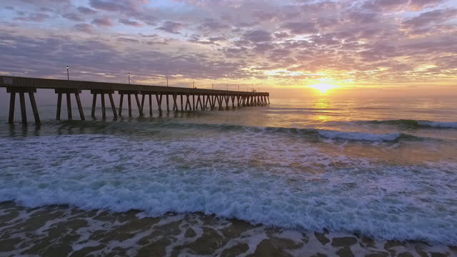 drone. low level aerial view of johnny mercer's pier and waves crashing on shore during epic sunrise - north carolina beach stock videos & royalty-free footage