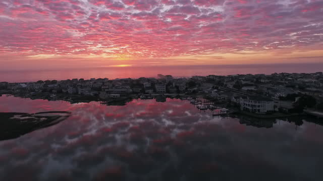 vídeos de stock e filmes b-roll de drone. low level aerial view of spectacular pink sunrise reflected on rippling waters in front of luxury beach houses at wrightsville beach - horizonte
