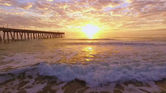 drone. low level aerial view of waves rolling to shore near johnny mercer's pier during epic sunrise - north carolina beach stock videos & royalty-free footage