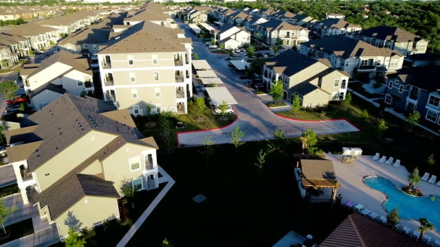 low near huge condo apartment buildings at sunset home ownership suburb drone view - stereotypically middle class stock videos & royalty-free footage