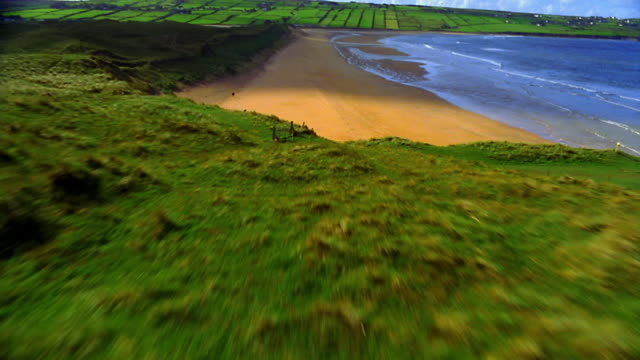 AERIAL low over hills + beach with farmland in background / Ireland