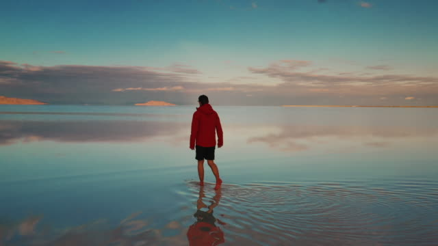low panning drone shot showing flooded bonneville salt flats and a person walking on them at sunset, utah, united states of america - reflection stock videos & royalty-free footage