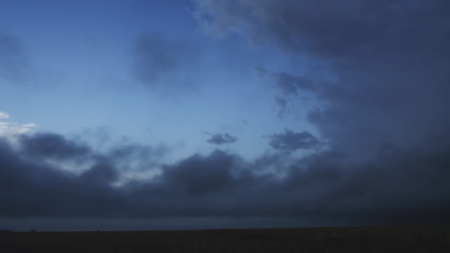 low ragged time-lapse clouds blow across the prairie at evening as a column of cloud rises at right - artbeats 個影片檔及 b 捲影像