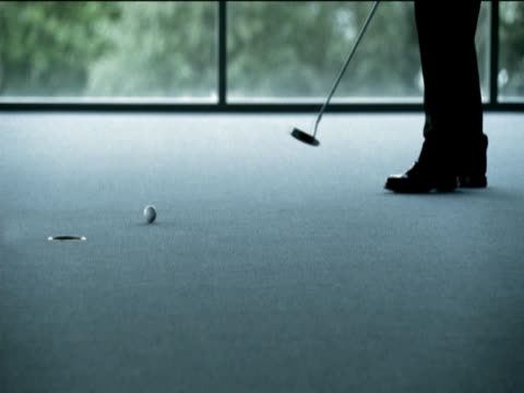 low section of a businessman putting a golf ball into a hole in the office floor then picking the ball up and walking away - ゴルフクラブ点の映像素材/bロール