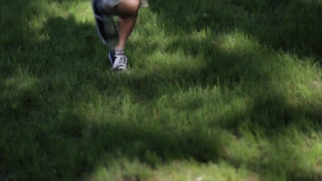 low section of boy running on grassy field - solo un bambino maschio video stock e b–roll