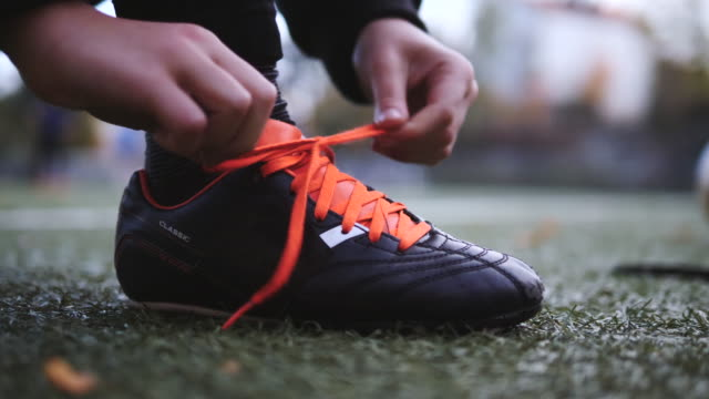 low section of boy tying shoelace on soccer field - tied up stock videos & royalty-free footage