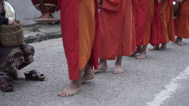low section of buddhist monks wearing saffron robes while walking barefoot on street in city - luang phabang, laos - off the beaten path stock videos & royalty-free footage