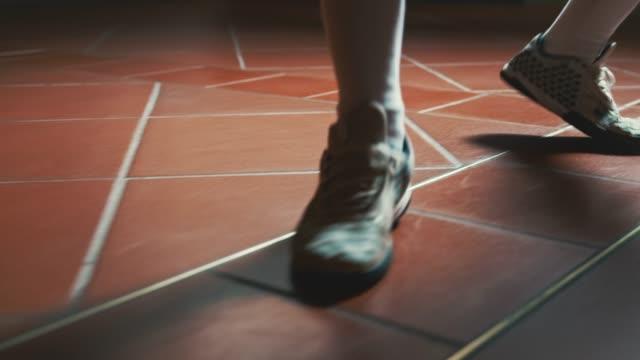 vídeos y material grabado en eventos de stock de sección baja del tirador que camina en el piso de baldosas - en guardia