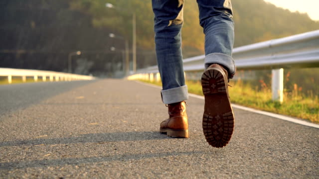 vídeos de stock e filmes b-roll de slo mo low section of man in boot walking in the morning - andar