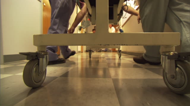 pov ms low section of medical stuff pushing gurney with patient through hospital corridor / burlington, vermont, usa - krankenhaus rollbett stock-videos und b-roll-filmmaterial