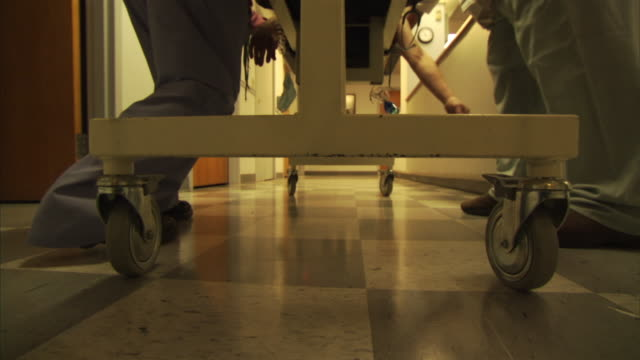 pov ms low section of medical stuff pushing gurney with patient through hospital corridor / burlington, vermont, usa - hospital trolley stock videos & royalty-free footage