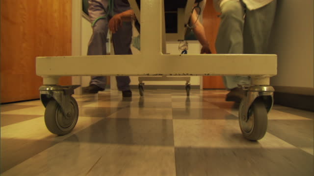 stockvideo's en b-roll-footage met pov ms low section of medical stuff pushing gurney with patient through hospital corridor / burlington, vermont, usa - ziekenhuisbed