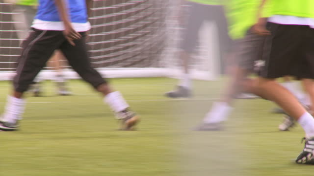 stockvideo's en b-roll-footage met cu low section of men playing soccer, london, uk - dribbelen