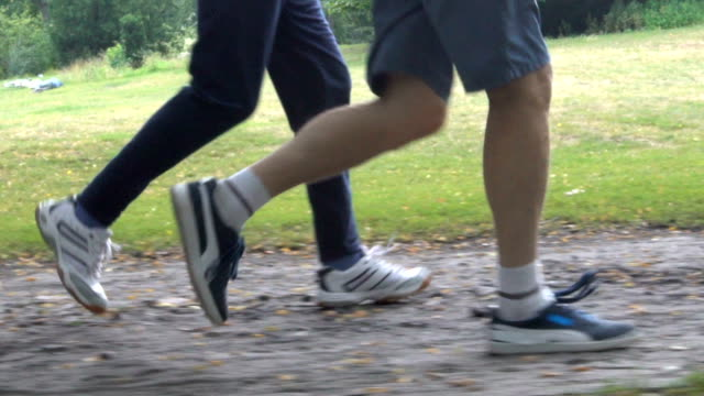 low section of senior men jogging on dirt road - low section stock videos & royalty-free footage