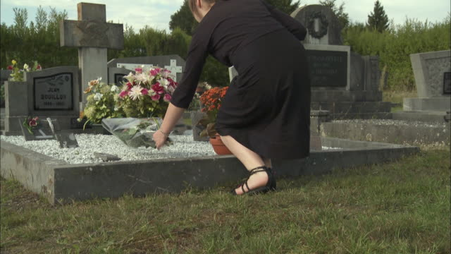 MS Low section of teenage girl (12-13) placing flowers on tombstone at cemetery, Latour, Belgium