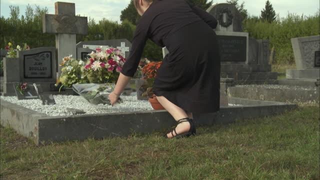 vidéos et rushes de ms low section of teenage girl (12-13) placing flowers on tombstone at cemetery, latour, belgium - cimetière