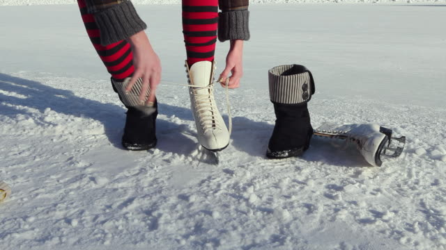 ms low section of teenage girl (14-15) putting ice skates on, standing on ice outdoors / gavle, gastrikland, sweden - leg warmers stock videos & royalty-free footage