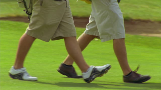 cu, pan, low section of two men walking on golf course, saco, maine, usa - golf shoe stock videos & royalty-free footage