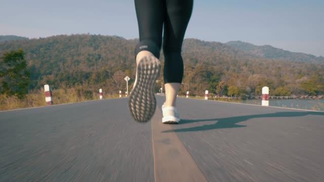 vídeos y material grabado en eventos de stock de sección baja de la mujer que corre en carretera - corredora de footing
