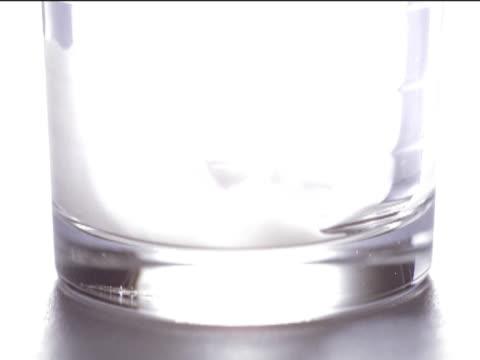 vídeos y material grabado en eventos de stock de low section shot of a glass being filled with milk - parte de